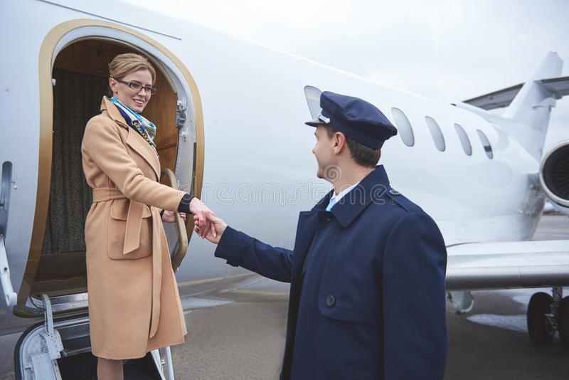 Cheerful lady greeting aviator outdoor royalty free stock images