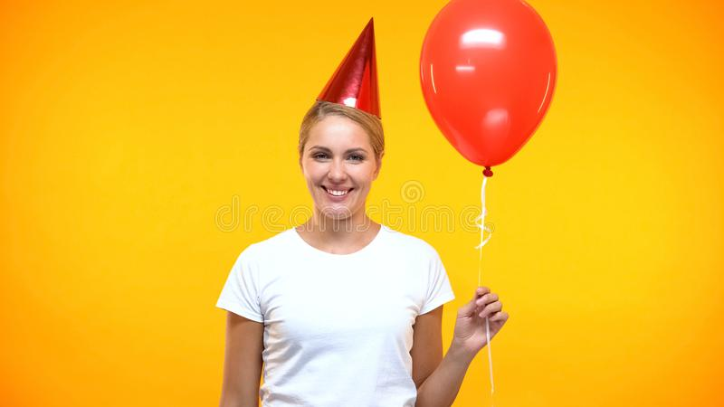 Cheerful lady party horn holding red balloon on bright background, holiday. Stock photo royalty free stock photo