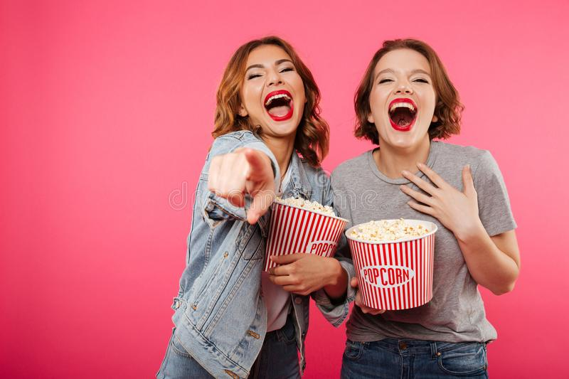 Cheerful laughing women friends eating popcorn watch film pointing. Image of two cheerful laughing women friends standing isolated over pink background. Looking royalty free stock photography