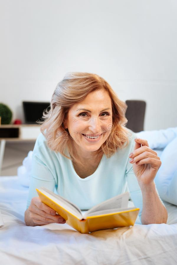 Cheerful light-haired woman resting on her bed and reading interesting book stock photo