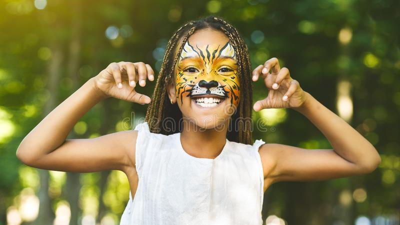 Cheerful little african-american girl with face painting like tiger. Scary tiger cub. Cheerful little african-american girl with face painting like tiger roaring royalty free stock photography