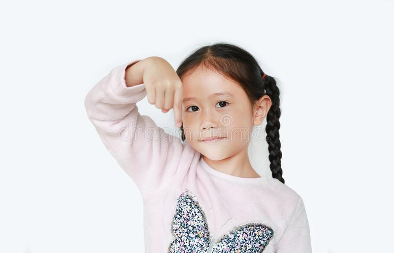Cheerful little Asian child girl points her one forefinger down over white background royalty free stock images