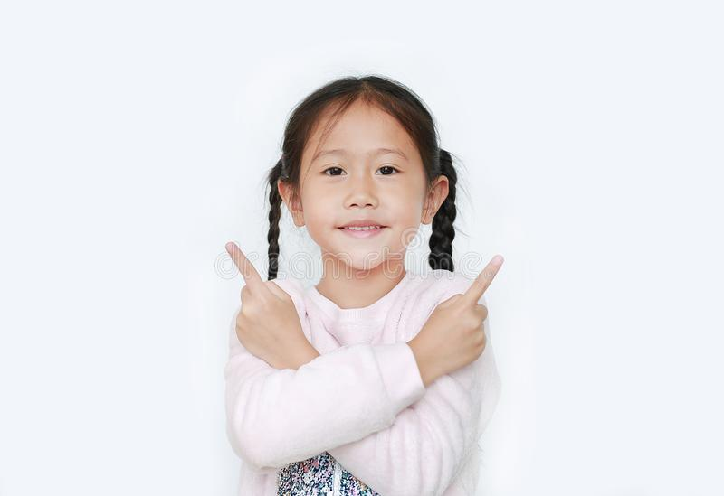 Cheerful little Asian kid girl cross arms and pointing two forefinger to the side over white background royalty free stock images