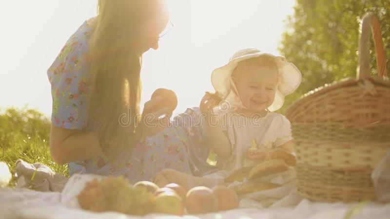 Cheerful little baby girl and her mom having picnic on a summer day royalty free stock images