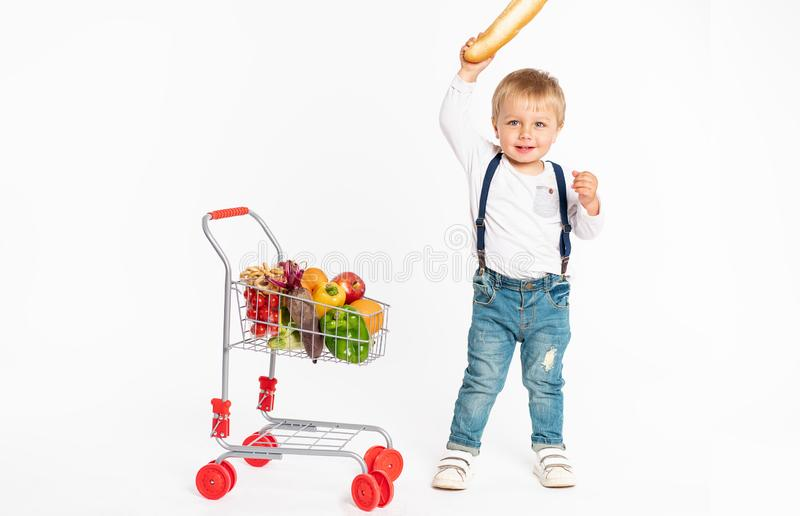 Cheerful little boy in casual clothes standing in studio with healthy food basket. Shopping, discount, sale concept stock photography