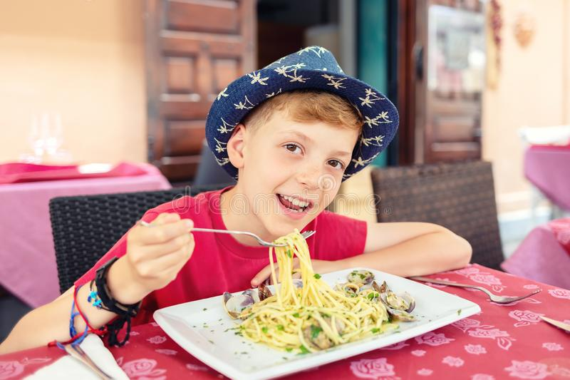 Cheerful little boy enjoying eating italian food - Portrait of happy smiling kid eating seafood pasta for lunch stock images