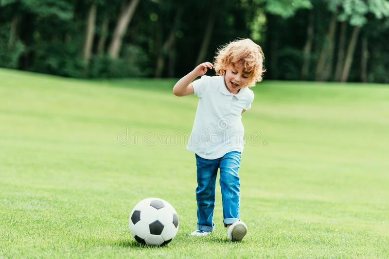 Cheerful little boy playing with soccer ball on green lawn. At park stock images