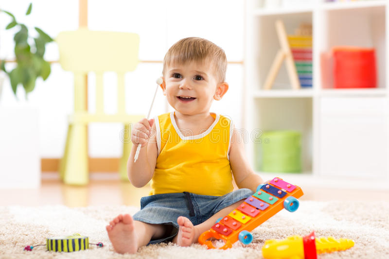 Cheerful little boy plays musical toys royalty free stock photography
