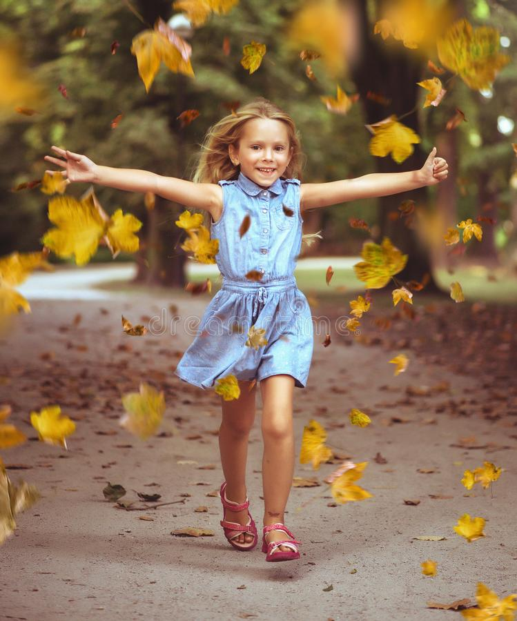 Cheerful little girl in an autumn colorful park stock images