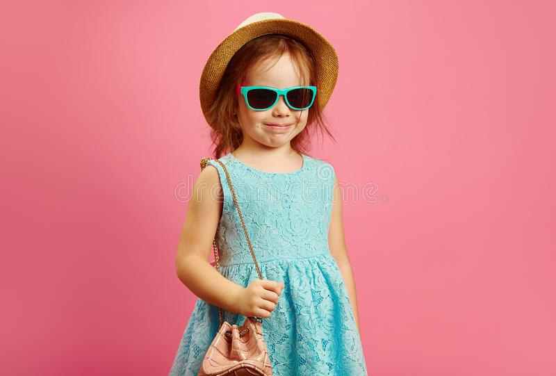Cheerful little girl in beach clothes and handbag, stands over pink isolated background, expresses joy and happiness stock images