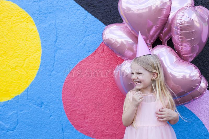 Birthday girl. Cheerful little girl with birthday cap on head and pink balloons on background stock images