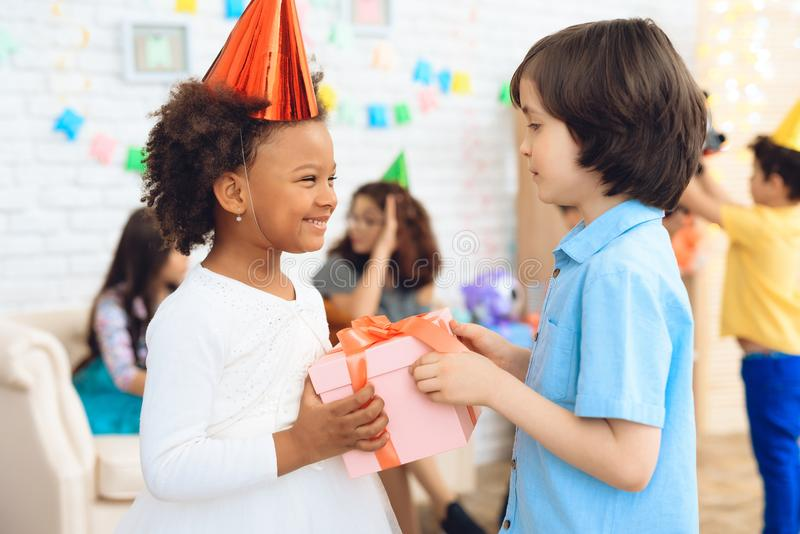 Cheerful little girl in birthday hat waits for her to receive gift box. Gift time. Cheerful little birthday girl waiting for gift stock images