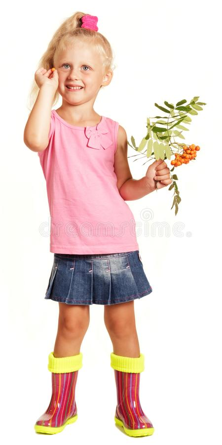 Cheerful little girl in blouse, skirt and rubber boots holding b stock photography