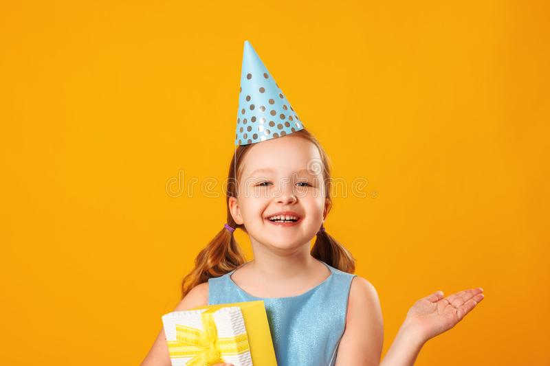Cheerful little girl celebrates birthday. A child in a blue dress and cap holds a box with a gift. Closeup portrait on yellow. Background royalty free stock photography