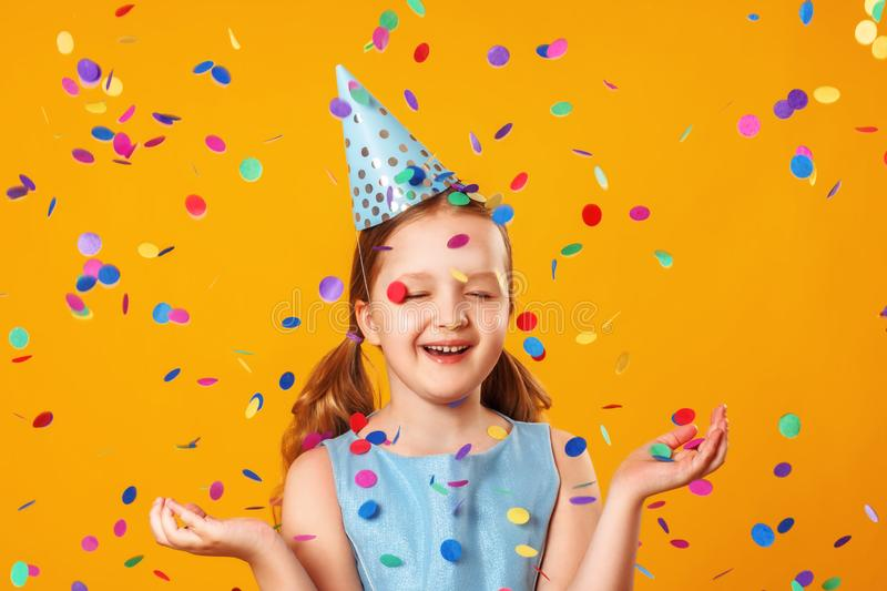 Cheerful little girl celebrates birthday. The child is standing with eyes closed in the rain of confetti. Closeup portrait on stock photos