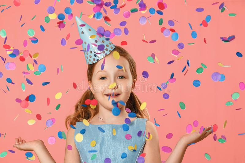 Cheerful little girl celebrates birthday. A child is standing in a rain of confetti. A party. Closeup portrait on pink background royalty free stock images