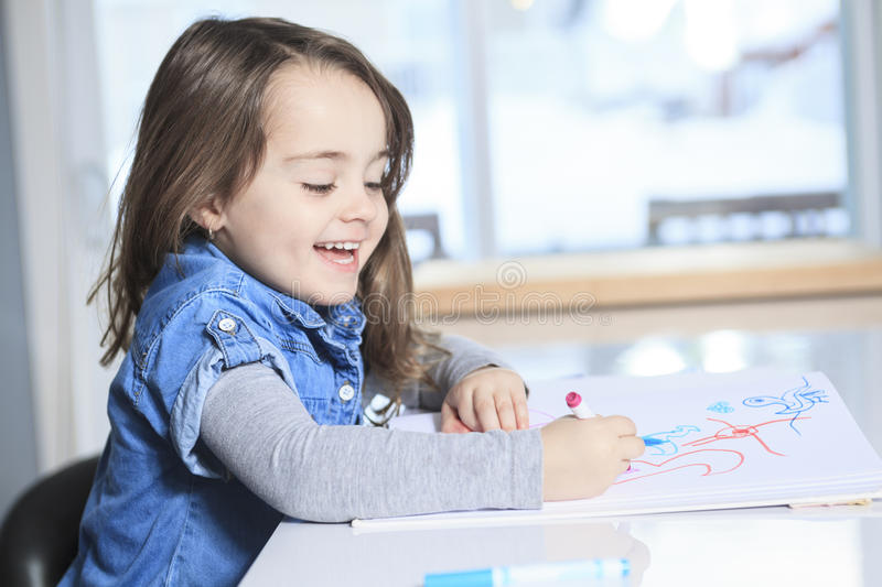 Cheerful little girl colouring at the table at. A Cheerful little girl colouring at the table at home in kitchen stock photography