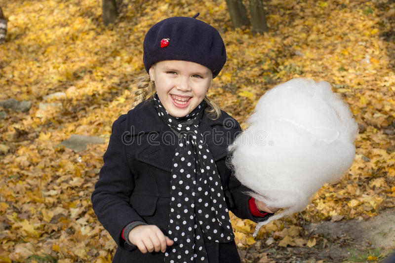 Cheerful little girl eating cotton stock images
