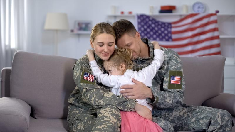 Cheerful little girl embracing US soldiers parents, family reunion, homecome stock images