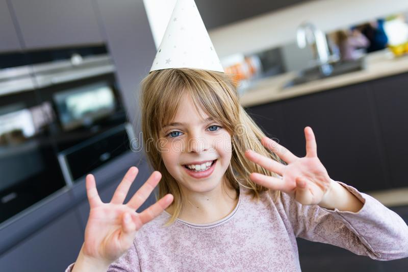 Cheerful little girl holding up eight fingers while celebrating her birthday in the kitchen at home royalty free stock image