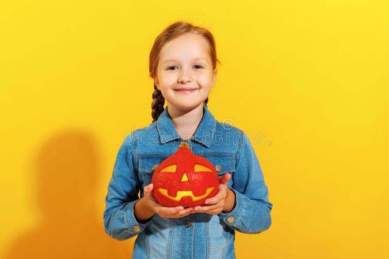 Cheerful little girl in a jeans shirt holds a pumpkin jack lantern on a yellow background. Halloween celebration stock photo