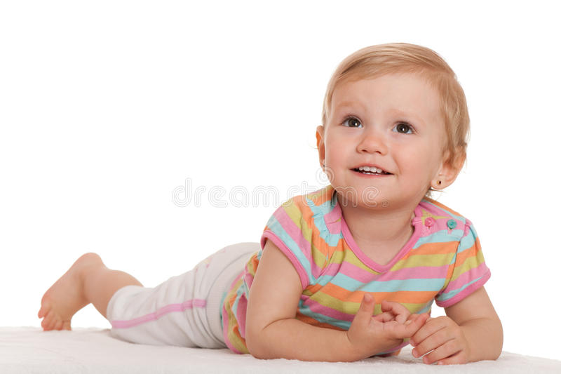 Cheerful Little Girl Lying On The White Looking Up Stock Photos