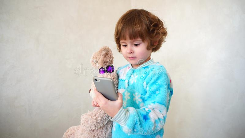 Cheerful little girl makes faces on mother`s phone. stock image