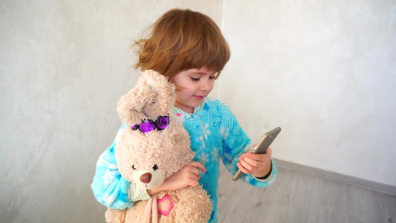 Cheerful little girl makes faces on mother`s phone. royalty free stock image