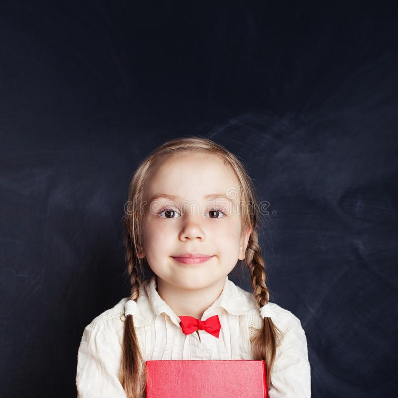 Cheerful little girl portrait. Beautiful child. On empty blackboard background with copy space royalty free stock photos