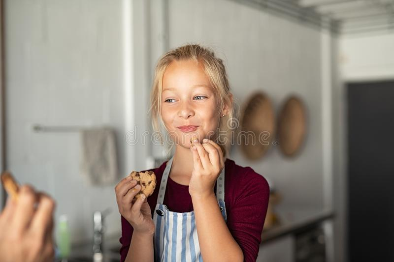 Funny cute girl eating chocolate cookie stock photo