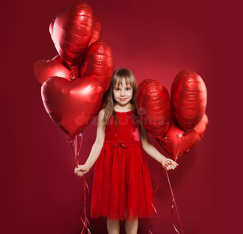 Cheerful little girl in tulle skirt holding balloons red heart on red background. Celebrating brightful carnival for kids stock photos