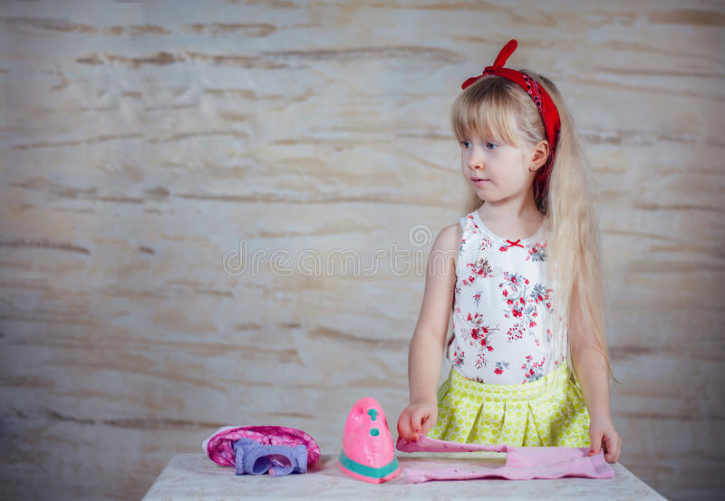 Cheerful little girl using toy iron royalty free stock photos