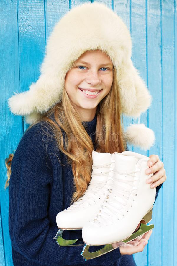 Cheerful little girl in warm sweater and hat keeps figure skates royalty free stock photo