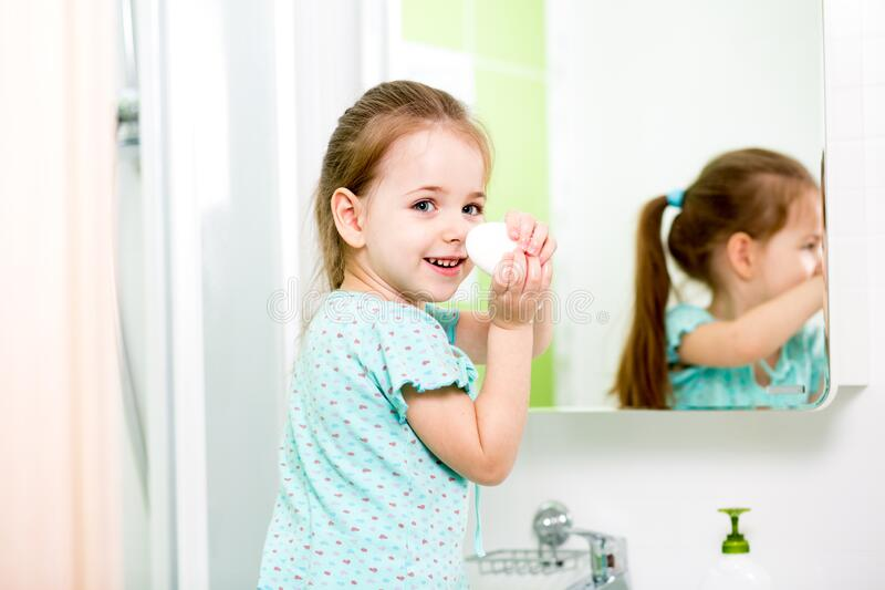 Little girl washing hands and showing soapy palms stock image