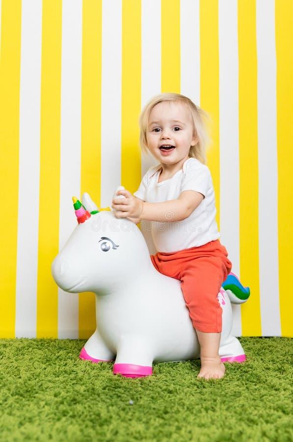 Bright Happy Little Girl on Toy Unicorn. Childhood. Background stock images