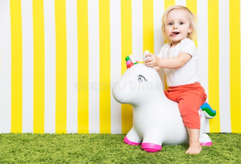Bright Happy Little Girl on Toy Unicorn. Childhood. Background stock image