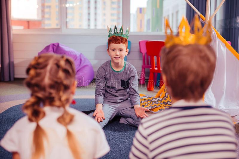 Cheerful little male person looking at his friends. Positive thoughts. Delighted kid expressing positivity while wearing paper crown royalty free stock photos