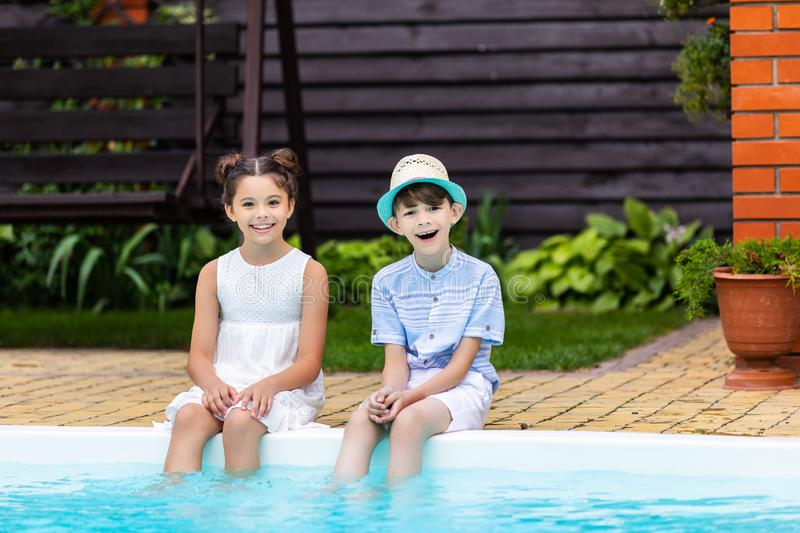 cheerful little siblings resting near swimming pool stock image