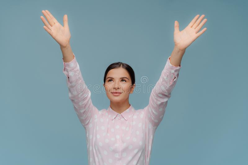 Cheerful lovely brunette female tries to catch something falling from sky, stretches hands focused upwards, shows palms, dressed stock photos