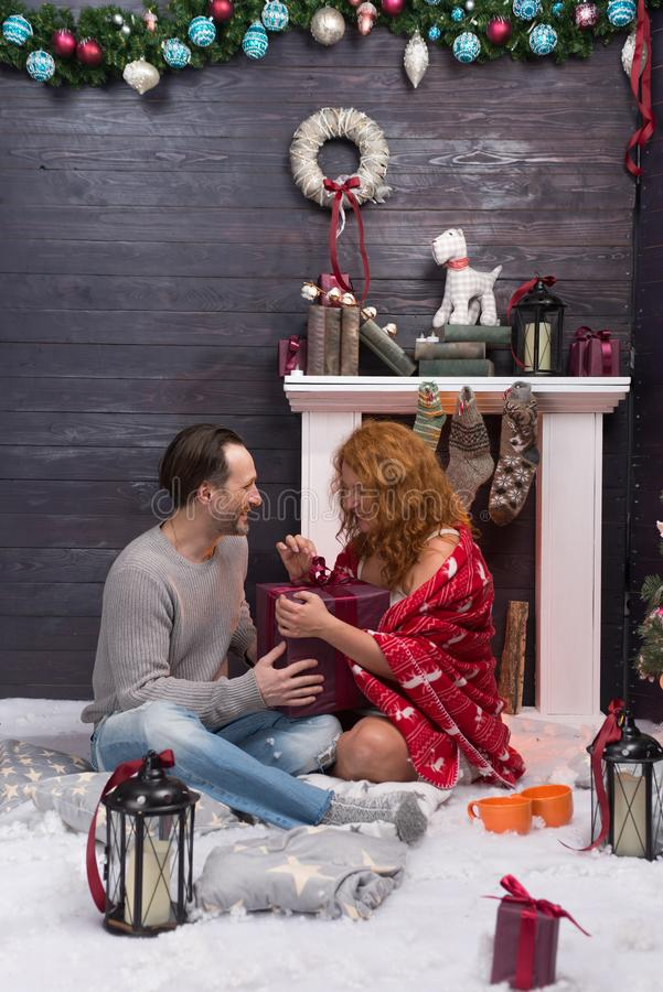 Romantic couple sitting near the fireplace and opening Christmas presents. Cheerful lovely couple smiling while sitting on white carpet near the fireplace and stock image
