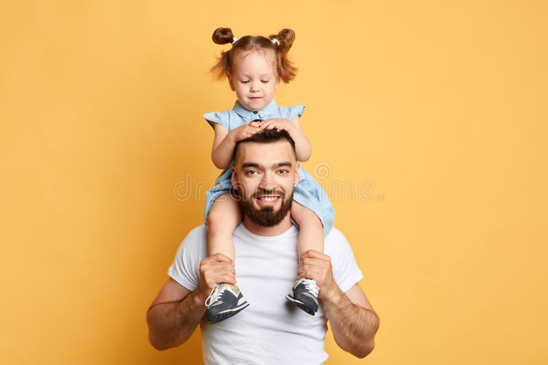 Cheerful lovely daughter sitting on father`s shoulders royalty free stock images