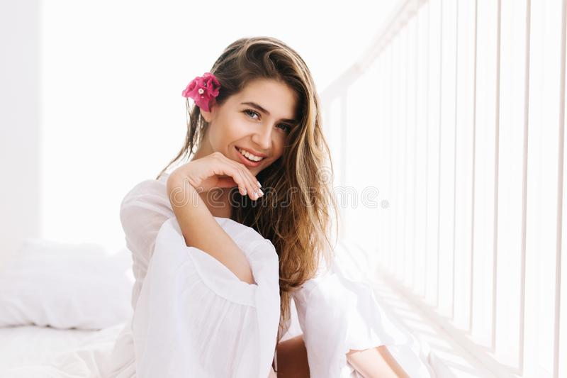 Cheerful lovely girl with amazing smile and romantic hairstyle gladly posing in white room. Portrait of cute young woman royalty free stock images