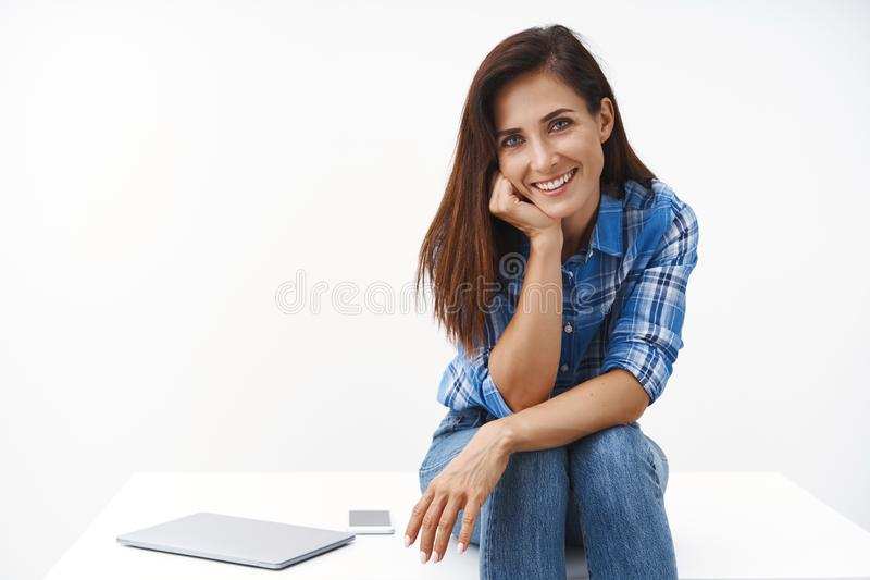 Cheerful lovely middle-aged woman sit table, have break from work, lean face palm, tilt head smiling enthusiastic royalty free stock photography