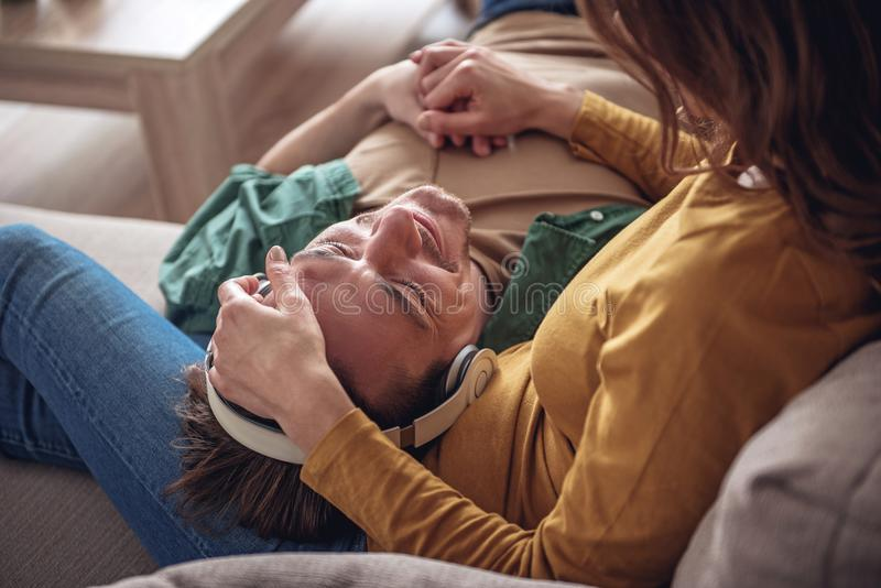 Glad husband listening to music while resting with wife stock photo