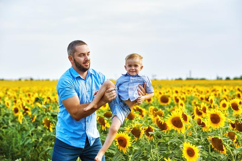 Cheerful loving father with his son on vacation in the field with sunflowers stock image