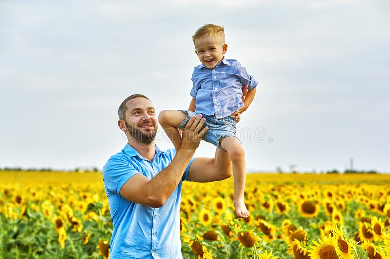 Cheerful loving father with his son on vacation in the field with sunflowers royalty free stock photography