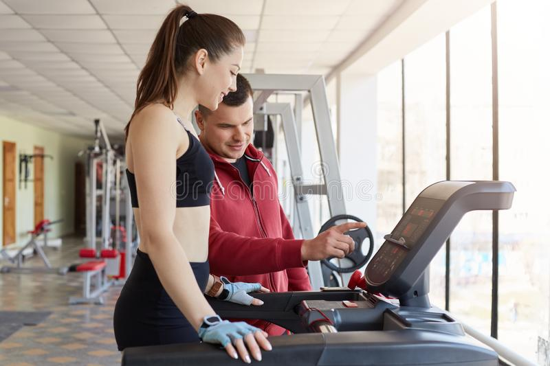 Cheerful magnetic young lady asking for help her trainer, trying to use running machine, listening to instructions carefully. royalty free stock photos