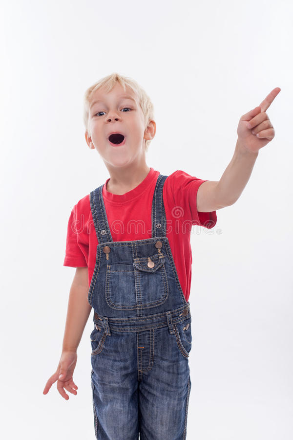Cheerful male child is showing something. Pretty blond boy is standing and smiling. She is pointing his finger sideways and opening his moth with surprise stock images