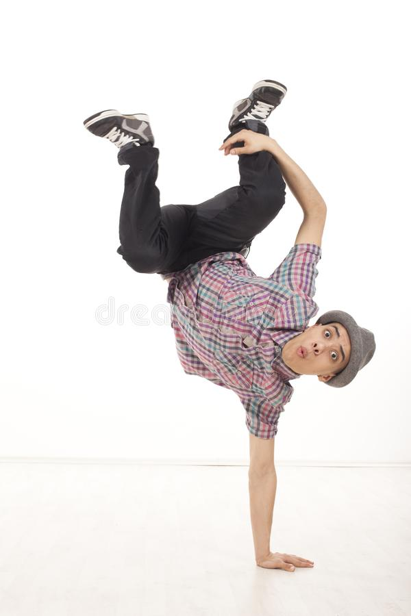 Cheerful male dancer sitting on one hand with legs up. Cheerful young man wearing casual shirt dancing sitting on one hand, performing breakdance moves on wood stock image