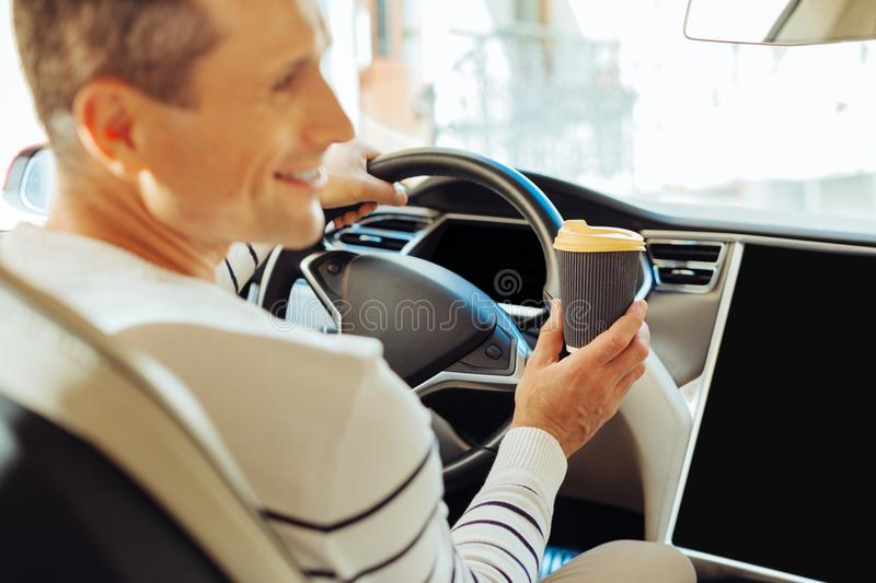 Cheerful male driver holding a cup of coffee. I need to wake up. Cheerful nice male driver smiling and holding a cup of coffee while sitting behind the wheel royalty free stock image
